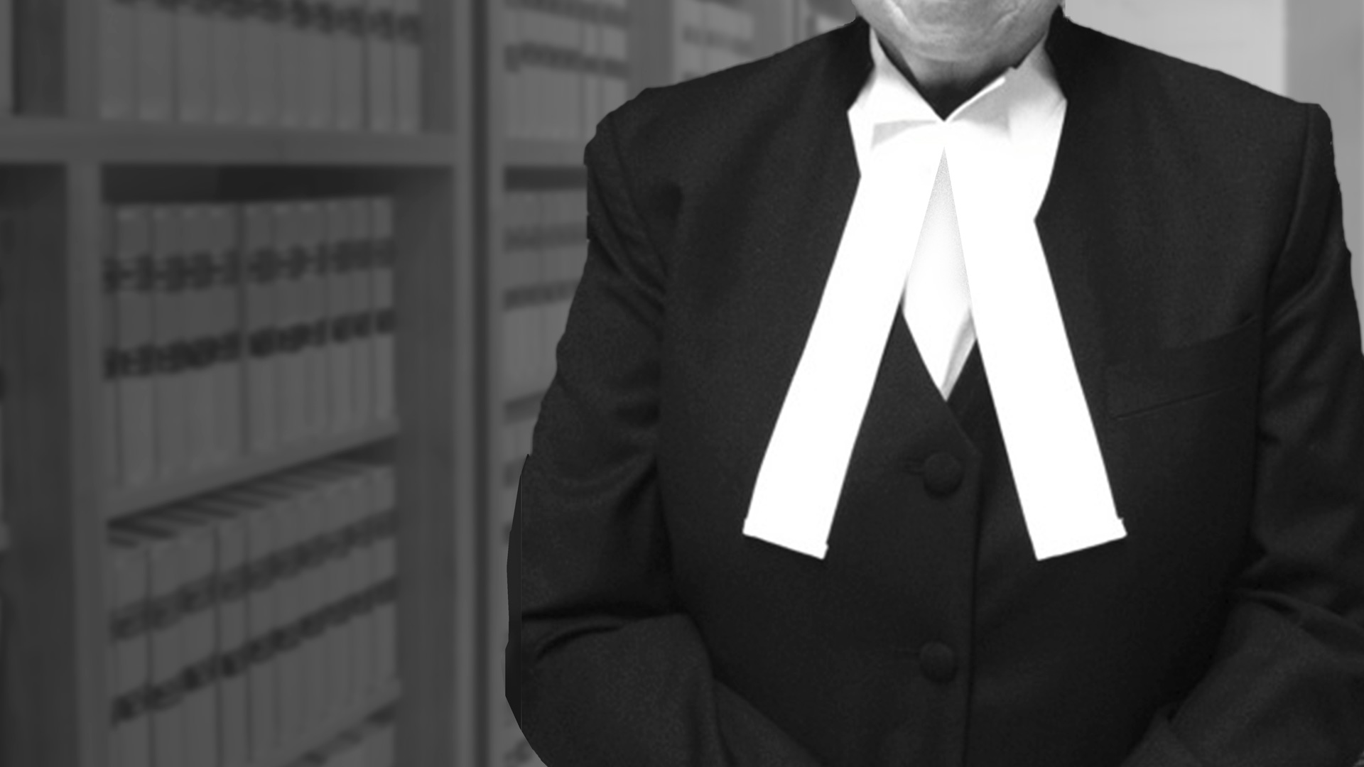 Our Barristers - photo of barrister standing in front of a bookcase